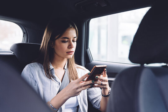 Pensive young woman using smartphone in car