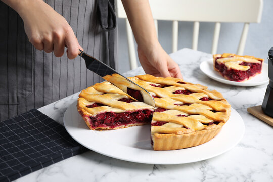 Woman cutting tasty cherry pie at white marble table, closeup