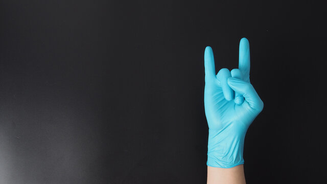Hand is wear blue glove and doing i love you hand sign on black background.