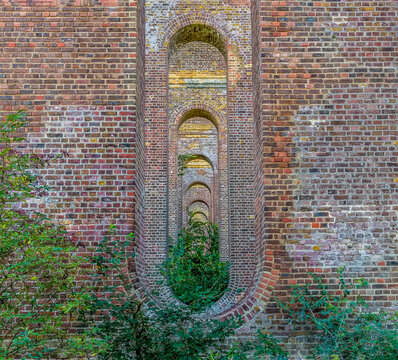 A view of concentric oblong apertures in the towers of the Chappel Viaduct near Colchester, UK in the summertime