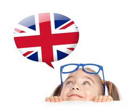 Beautiful cute little girl hiding under table and curiously looking at the UK flag speech balloon above her head. Learning english concept.