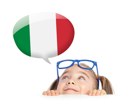 Beautiful cute little girl hiding under table and curiously looking at the Italy flag speech balloon above her head. Learning italian concept.