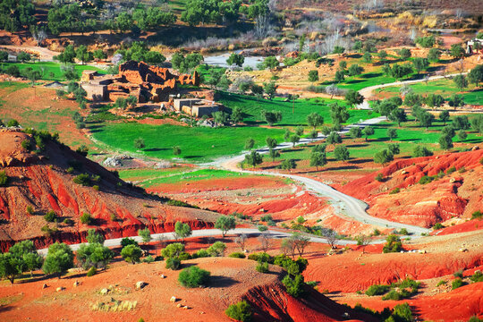 Draa-Tafilalet region, Morocco, North West Africa. Beautiful nature view, a twisty country road among green fields, trees, red hills and ruined ksar - fortified village, Moroccan clay architecture