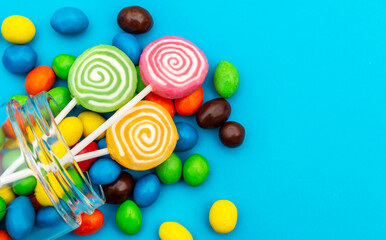 Candies scattered from glass jar on blue background. Close up. Space for text.