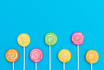 Lollipops on stick on blue. Copy space. Top view. Holiday background.