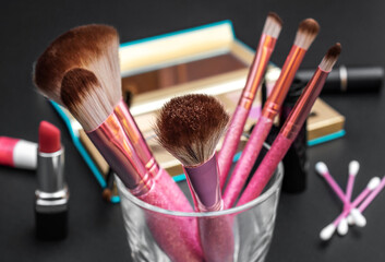 Professional makeup brushes with other cosmetics tools on black desk.
