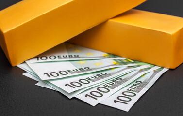 Gold bullions wit euro bills on black. Business concept.