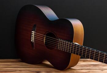 Classical acoustic guitar lying down on floor near blackwall.