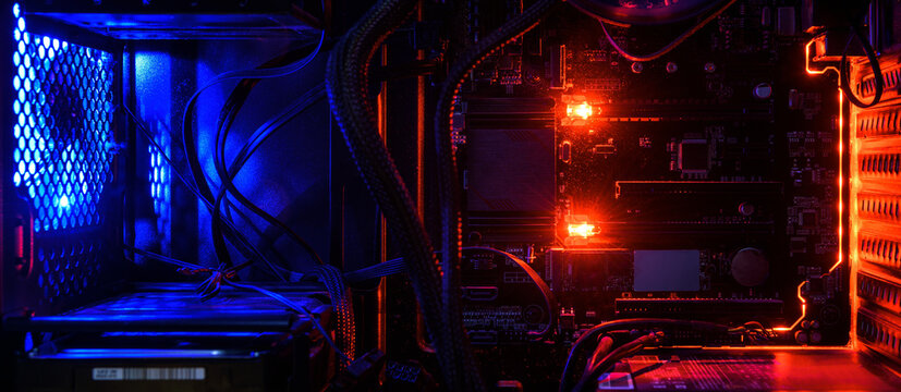Computer with circuit board and internal LED RGB lights, hardware inside open high performance desktop PC.