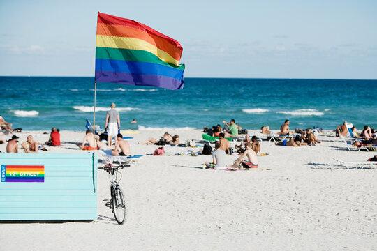 Gay pride flag fluttering on the beach, Miami Beach, Florida, USA