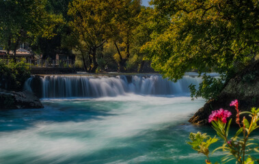 View of flowing Manavgat Waterfall in Antalya, Turkey, with green trees around, on cloudy blue sky background. July 2020, long exposure picture