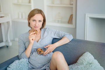 Pregnancy and nutrition. Pregnant woman enjoying cookies in bed