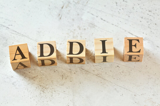 Five wooden cubes with letters ADDIE (means Analysis Design Development Implementation Evaluation) on white stone like board, view from above