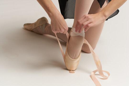 Ballerina puts pointe shoes on her feet White ribbon model dance light background.