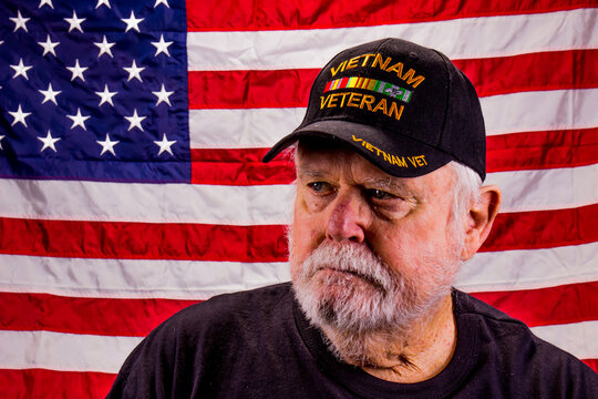 Vietnam Veteran Looking Away Suspiciously With American Flag Background