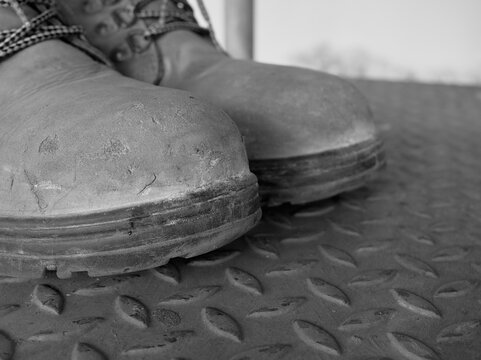 Isolated pair of safety shoe or steel-toe boots used for construction purpose.