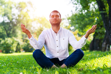 Young man meditates in lotus pose on green grass