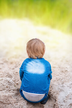 Child in denim suit plays in the sand by the river. Back view.