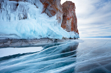 Baikal Lake in winter cold day. Beautiful landscape with a blue smooth ice with cracks near the rocky coast of Olkhon Island. View of the icy cliffs Three Brothers. Winter travels. Natural background