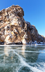 Baikal Lake on a sunny February day. View on Shibete Mountain from smooth blue ice with cracks. Beautiful winter landscape. Ice travel. Natural background