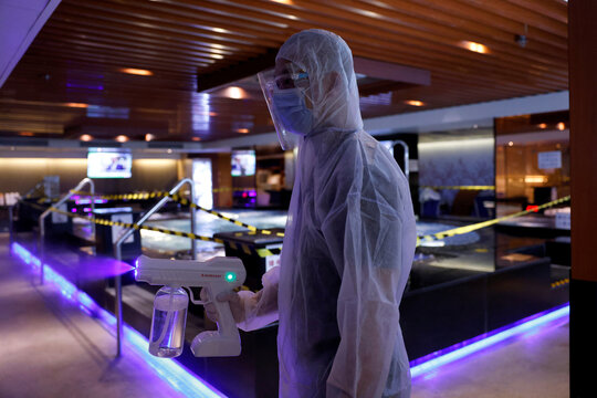 A cleaner wearing a protective suit sprays disinfectant at a Sauna & Spa centre to prepare the reopening, following the coronavirus disease (COVID-19) outbreak, in Hong Kong