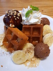 Dessert sweets concept. Waffers with ice cream, decorate with banana and whip cream on white plate.