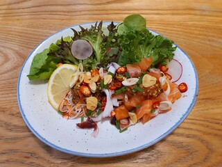 Salmon spicy salad, mixed with squids, crab sticks and Thai herbs on white plate. Healthy meal concept.