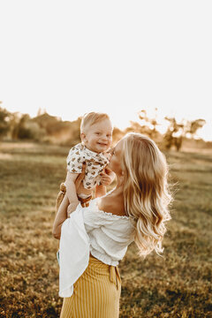 Mother holds baby boy in her arms in a field at gold sunset. Happy male kid smiling and laughing together with mom on nature background. Vertical photo