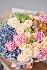 Autumn bouquet of mixed flowers on wooden table. The work of the florist at a flower shop. Fresh cut flower.