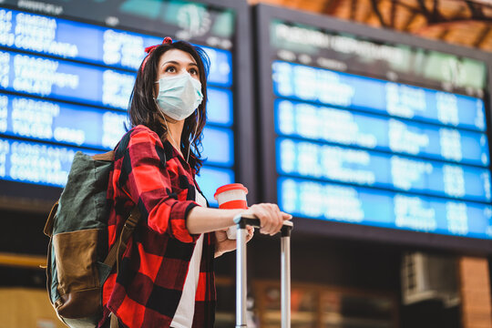 Young woman wearing protective face mask standing against information panel at airport or train station