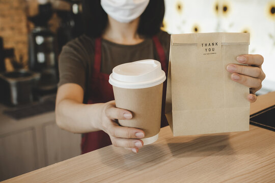 waitress wearing protection face holding hot coffee cup and paper bag waiting for customer in modern cafe coffee shop, food delivery, cafe restaurant, takeaway food, small business owner concept
