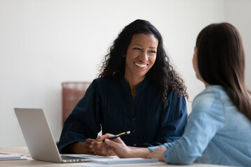Fototapeta Smiling African American businesswoman talking to colleague, diverse employees brainstorming, sitting at table in office, manager consulting client, using laptop, mentor coach training intern obraz