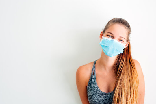 portrait of a girl in sportswear wearing a protective mask against covid virus with positive attitude