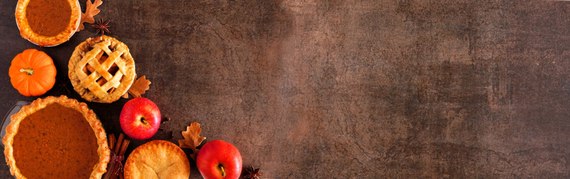 Variety of homemade autumn pies. Pumpkin, apple and pecan. Above view corner border on a dark stone banner background with copy space.