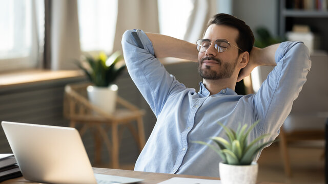 Calm millennial man in glasses sit relax at home office workplace take nap or daydream. Happy relaxed Caucasian young male rest in chair distracted from computer work, relieve negative emotions.