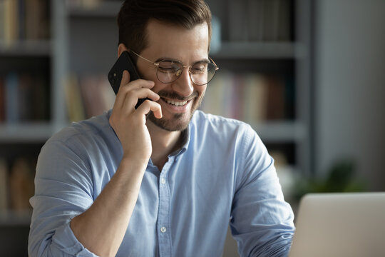 Smiling millennial Caucasian man laugh joke talking speaking on cellphone using laptop. Happy young male employee in glasses have pleasant smartphone call conversation with client or business partner.