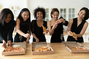 Happy young festive mixed race pretty women best friends in classic black dresses having fun at party, eating delivery italian fast food pizza, drinking champagne, enjoying meeting together indoors.