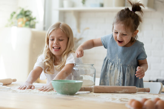 Two adorable sisters having fun in the kitchen. Cute mischievous 5 and 8 year old girls playing with flour and making mess after rolling the dough for muffins on wooden kitchen counter