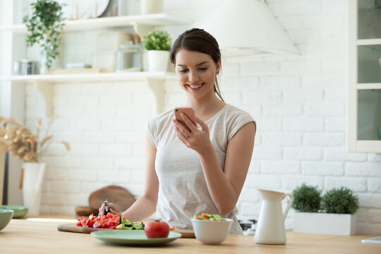 Smiling young woman making salad and using mobile to count calories and plan diet. Happy housewife consulting recipe instructions on smartphone while chopping vegetables in modern kitchen