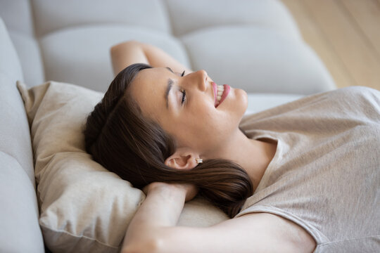 Happy relaxed woman lying on couch with eyes closed and enjoying peace and quiet of her own soundproof house. Good-looking young lady lounging on sofa cushion and smiling feeling content and fulfilled