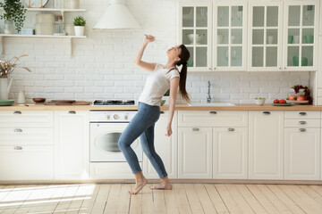 Cheerful young lady having fun alone at home. Happy housewife singing loudly in kitchen pretending whisk is a mic. Elated young woman dancing barefoot on heated wooden floor in her cozy kitchen