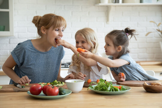 Playful kids feeding happy mum with carrots while chopping vegetables on cutting boards in the kitchen. Positive young mother teaching her 5 and 8 year old daughters to maintain healthy eating habits