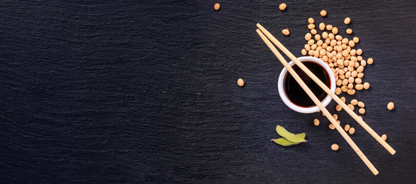 Soy sauce in a bowl with bamboo chopsticks and soya beans scattered on the black surface of the slate stone, banner, top view, closeup with space for text