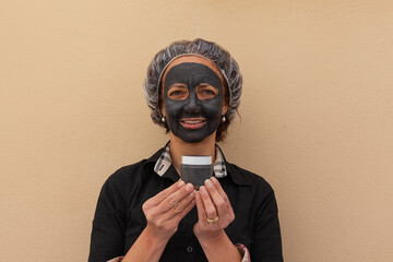 Smiling Brazilian woman with mud mask holding a jar of cream