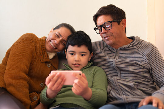 Lovely latin multigenerational family with smart phonewatching photos on mobile smart phone Indoors at home living room. Unity, happiness, affection, love, care concept.