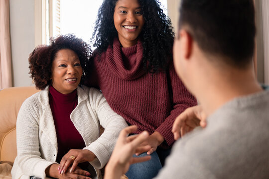 Happy cheerful latin mother and daughter sitting and listening boyfriend talking Indoors at home living room. Unity, happiness, affection, love, care concept..