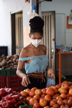 Young black latin woman buying vegetables in face mask