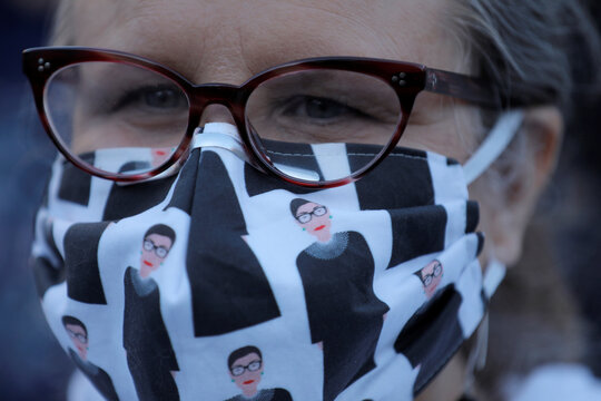 A woman wears a face mask featuring images of recently passed Associate Justice of the Supreme Court of the United States Ruth Bader Ginsburg during for a vigil held in Ginsburg's honor in Washington Square Park in Manhattan, New York City