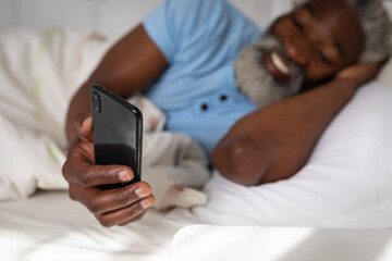 Man having a video chat on his smartphone in bed at home