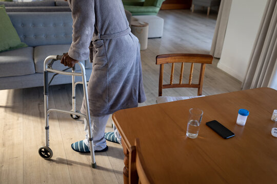 Mid section of senior man using zimmer frame to walk at home